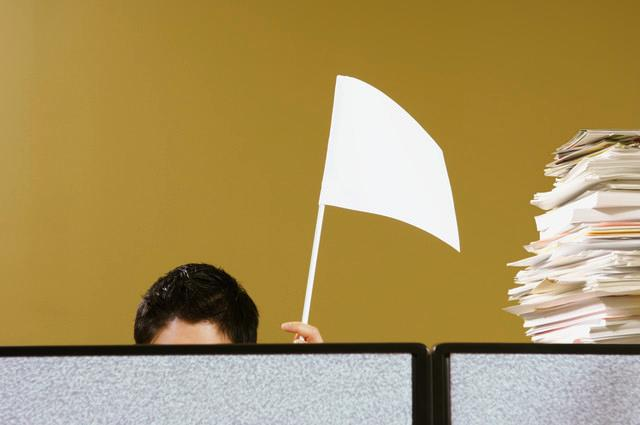 Businessman waving white flag from behind cubicle, Monalyn Gracia/Corbis