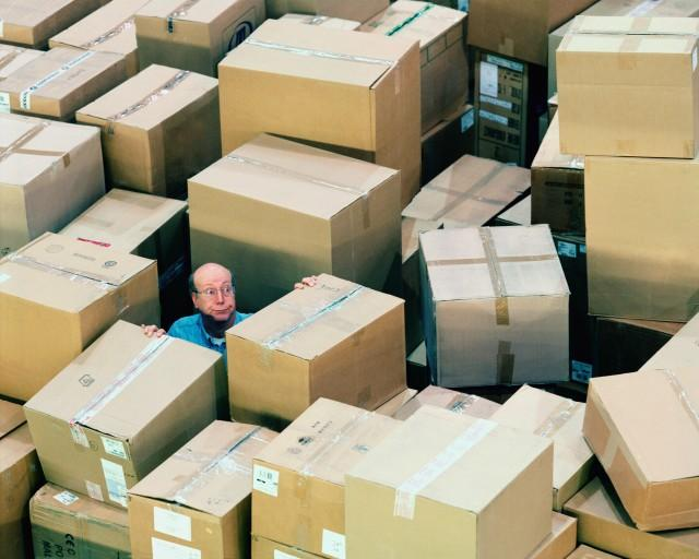 Man in warehouse surrounded by boxes, overhead view, Ocean/Corbis