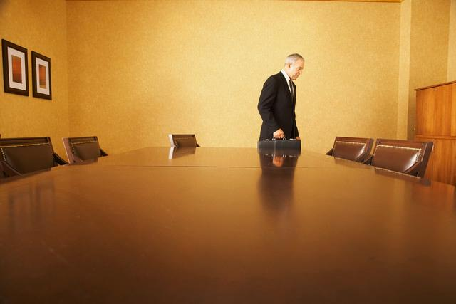 Businessman walking away from conference table, Plush Studios/Bill Reitzel/Blend Images/Corbis