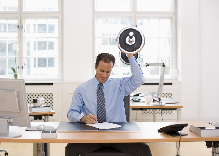 Businessman lifting weights in office, Creasource/Corbis