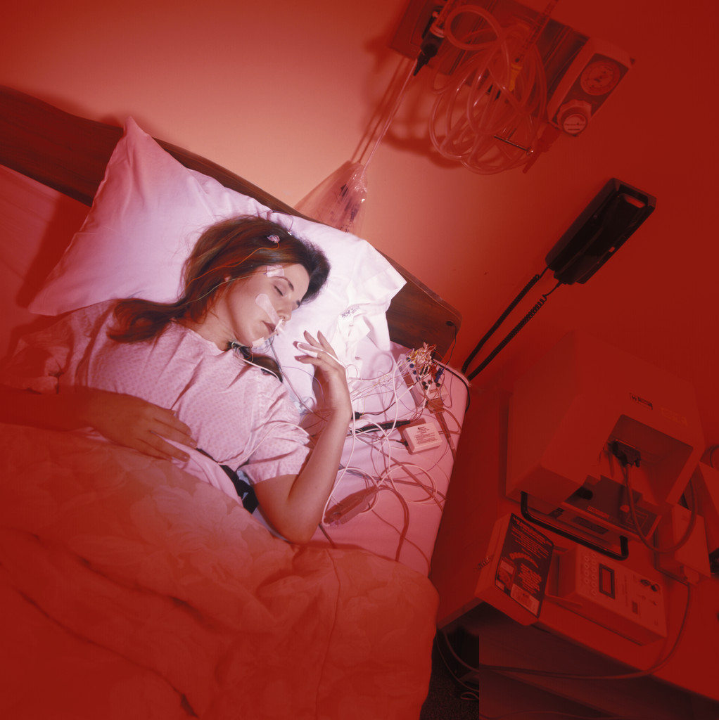 Young Female Patient Asleep in a Sleep Research Laboratory With Red Lights, Yoav Levy/Science Faction/Corbis