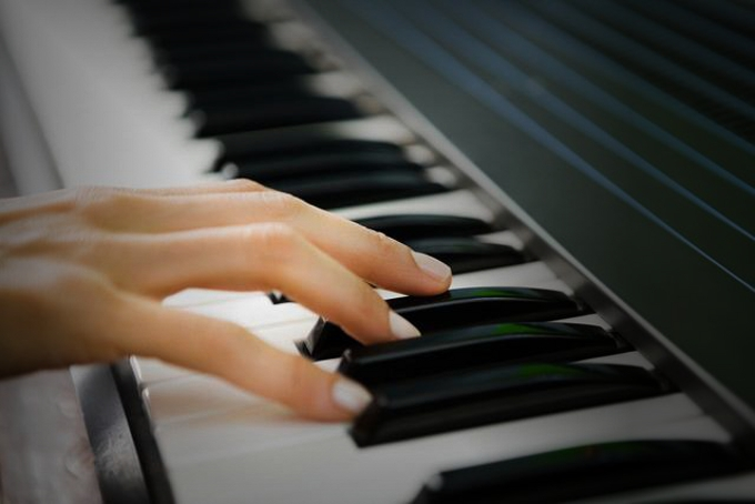 Hand playing a piano, lowimages/Corbis