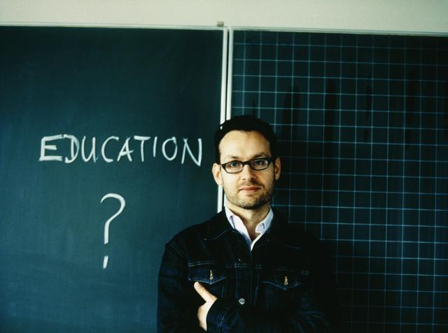 Teacher in front of black board, Martin Meyer/Corbis