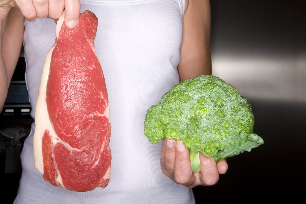 Close up of woman holding fresh meat and frozen broccoli, Image by Juice Images/Corbis