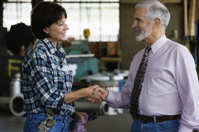 Businessman shaking hands with female warehouse worker, Image by ColorBlind Images/Blend Images/Corbis