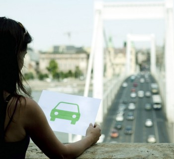 Woman holding paper green car, Image by Chev Wilkinson/cultura/Corbis
