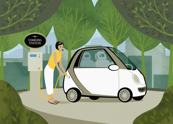 Woman recharging her electric car among trees, Image by Ikon Images/Corbis