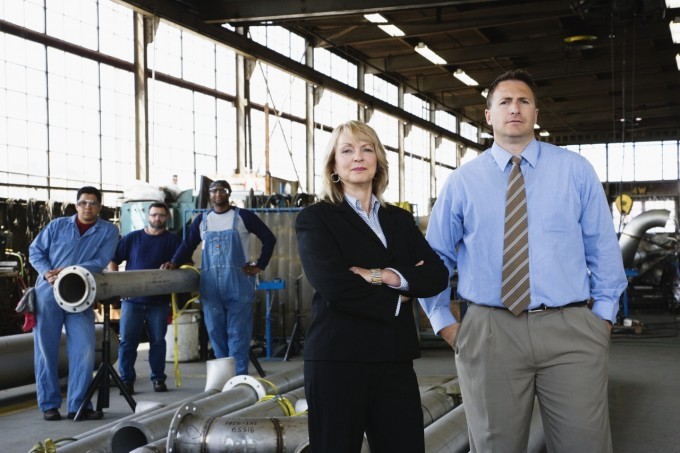 Businesspeople and Workers in a Factory, Image by © Corbis