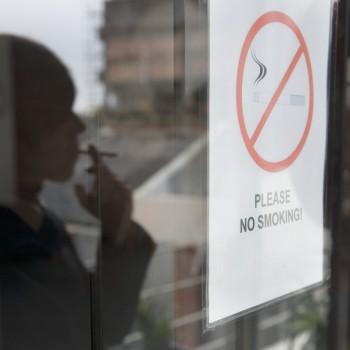 """Person Smoking Near """"No Smoking"""" Sign, Image by © Roy McMahon/Corbis"""