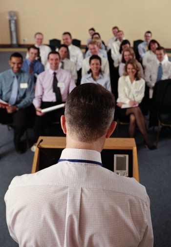 Businessman speaking at podium, rear view, Image by © Ocean/Corbis