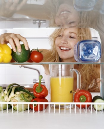Woman Taking a Green Pepper from a Fridge Rack, Image by © Ocean/Corbis
