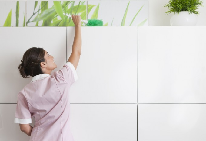 Maid dusting cabinet, Image by © DreamPictures/VStock/Blend Image/Blend Images/Corbis