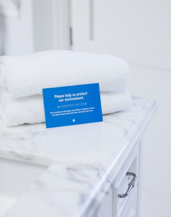 Tag in front of folded towels in hotel bathroom, Image by © Rana Faure/Corbis