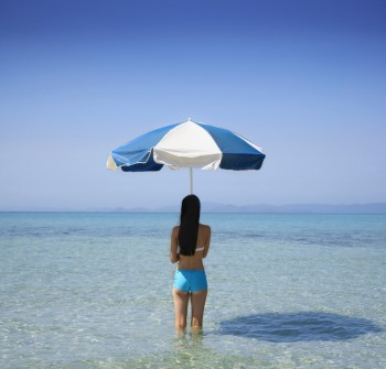 Pacific Islander woman holding beach umbrella in ocean, Image by © Colin Anderson/Blend Images/Corbis