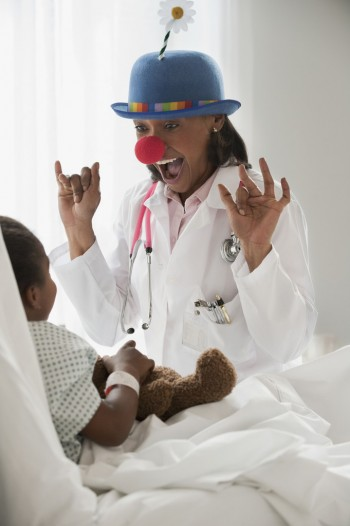 Doctor entertaining girl in hospital bed. Image by © Jose Luis Pelaez Inc/Blend Images/Corbis