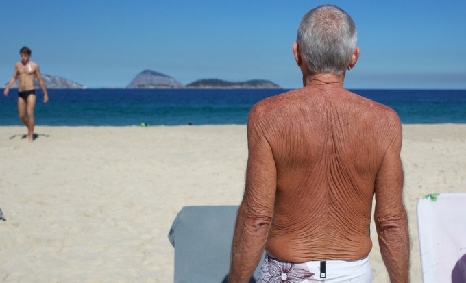 A man with sunbaked skin on the beach at Ipanema, Rio de Janeiro,  Brazil, Image by © Tim Clayton/Corbis