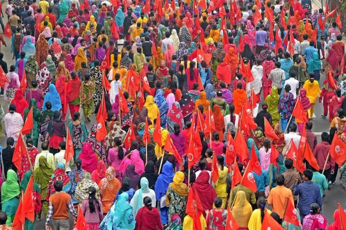 L'incendio che scoppiò a Dhaka il 24 novembre 2012, nella fabbrica di moda di Tazreen nel distretto di Ashulia alla periferia di Dhaka, ha portato una pressa di coscenza dei lavoratori tessili che tengono bandiere rosse durante una manifestazione con lo scoppo di chiedere la sicurezza nei luoghi di lavoro. Dhaka, Bangladesh. 1° febbraio 2013 - Image by © firoz ahmed/Demotix/Corbis