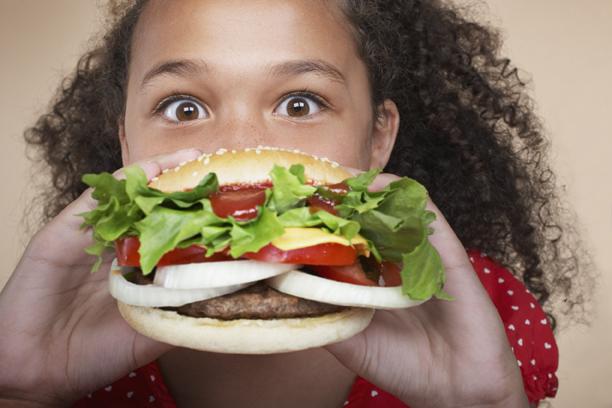 Ragazza che mangia hamburger