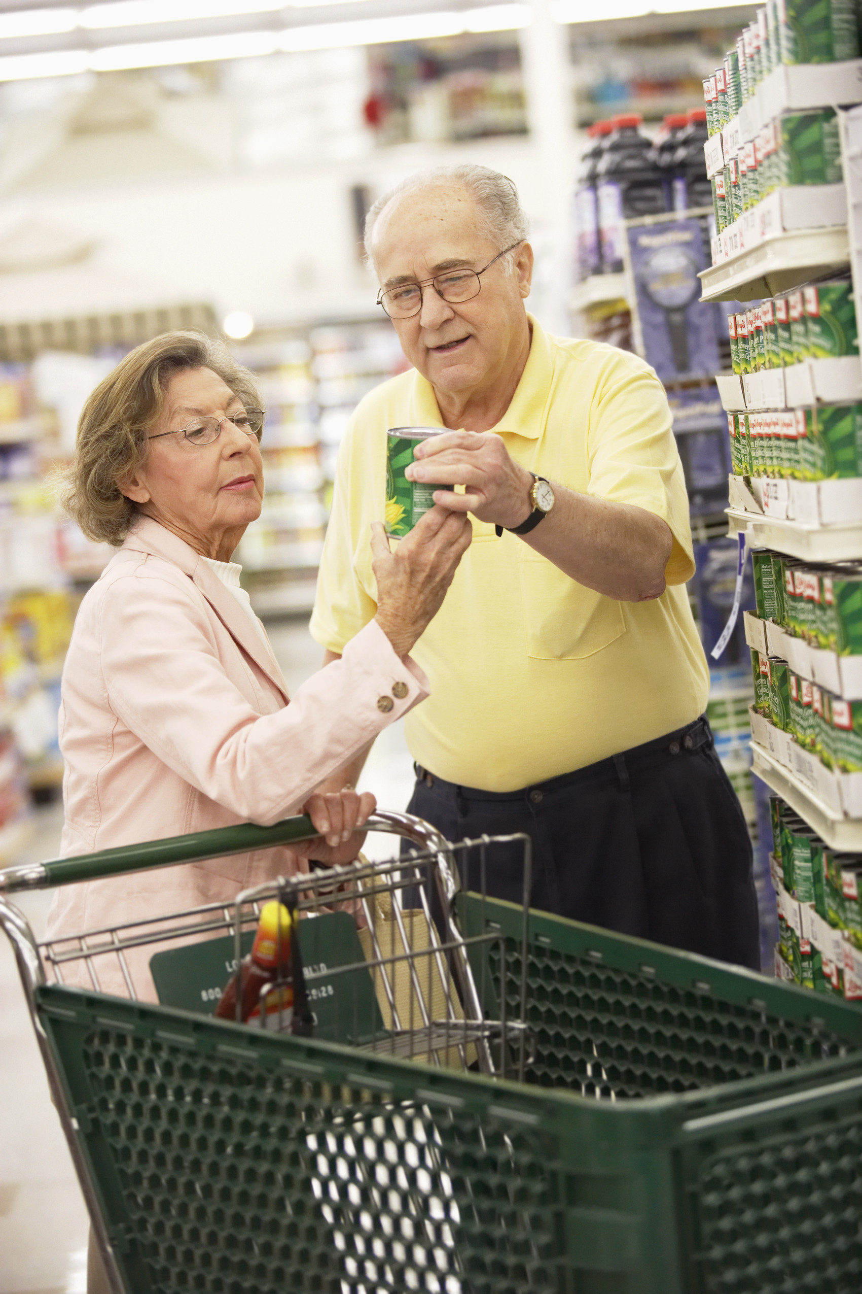Couple Reading Canned Food Label --- Image by © PictureNet/Corbis