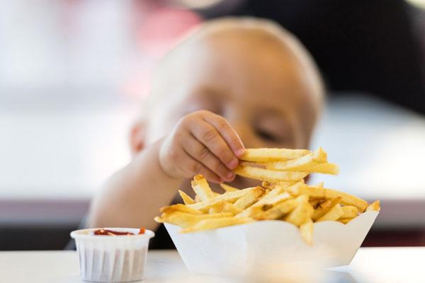 Bambino che mangia patatine