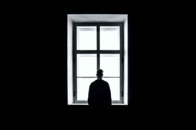 Uomo davanti a una finestra: rappresentazione della depressione