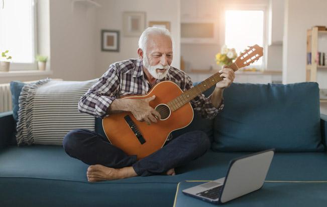 Un anaziano segue un corso di chitarra via Internet
