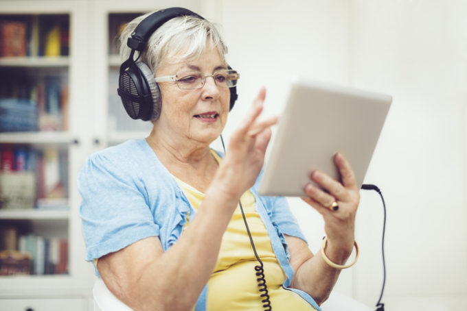 Una signora anziana gioca col suo tablet
