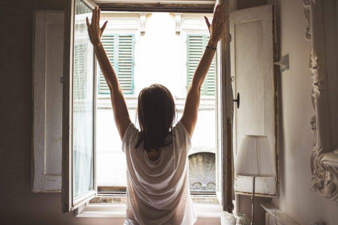Ragazz di spalle davanti ad una finestra di casa aperta