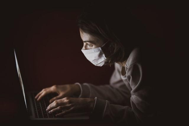 persona con mascherina davanti al computer