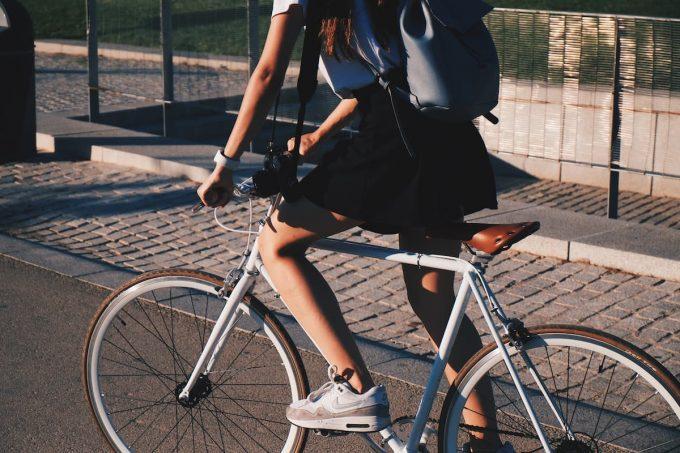 Ragazza in bicicletta su pista ciclabile