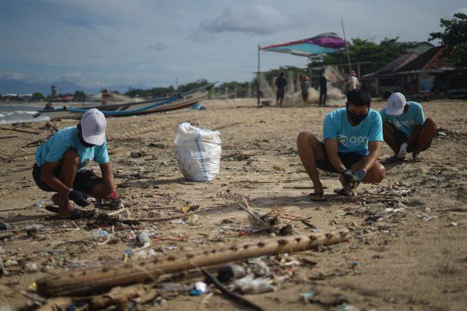 Volontari che raccolgono plastica in spiaggia
