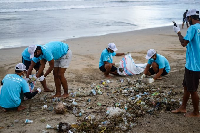 Uomini che ripuliscono spiaggia da marine litter